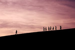 A person is leading a group of people down from a hill during sunset